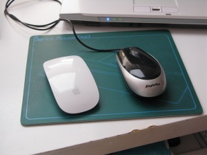 Apple Magic Mouse and USB mouse side by side.